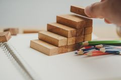 De mensen` s hand zette houten blokken in de vorm van een trap royalty-vrije stock afbeeldingen