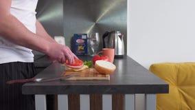 De mensen` s handen bereiden een hamburger voor stock videobeelden