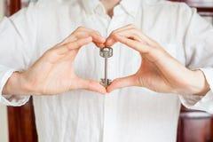 De mensen` s handen houden huissleutel in de vorm van hart op de achtergrond van een houten deur Het bezitten van onroerende goed royalty-vrije stock afbeeldingen