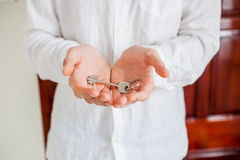 De mensen` s handen houden huissleutel op een achtergrond van een houten deur Het bezitten van onroerende goederenconcept Royalty-vrije Stock Afbeelding