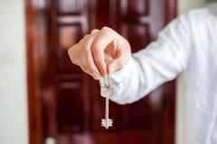 De mensen` s handen houden huissleutel op een achtergrond van een houten deur Het bezitten van onroerende goederenconcept Royalty-vrije Stock Foto's