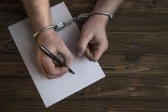De mensen` s handen met handcuffs vullen het strafblad, bekentenis royalty-vrije stock foto's