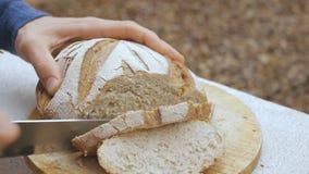 De mensen` s handen snijden een brood van brood stock video
