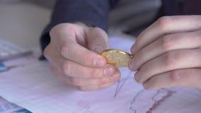 De mensen` s handen verdraaien in hun handen een gouden muntstuk van bitcoin groen in bureau stock footage