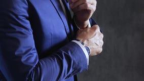 De mensen` s stijl, fiance maakt het dichtknopen en cufflink op kokers van overhemd op grijze concrete muur als achtergrond vast stock video