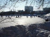 De mensen schaatsen op de piste en spelen hockey op een duidelijke Zonnige ijzige dag royalty-vrije stock fotografie