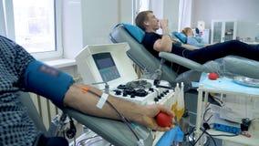 De mensen schenken bloed in een kliniek, zittend op medische stoelen stock footage
