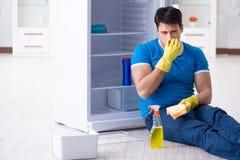 De mensen schoonmakende koelkast in hygiëneconcept stock afbeeldingen