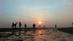 De mensen silhouetteren tijdens zonsopgang Stock Afbeeldingen