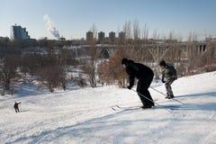 De mensen ski?en onderaan de heuvel in de stad Royalty-vrije Stock Fotografie