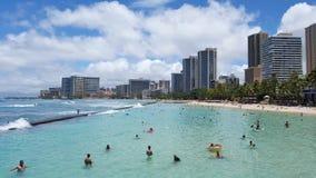 De mensen spelen in het beschermde water en hangen uit op het strand Stock Foto's