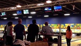 De mensen spelen kegelen in de het spelen zaal stock footage