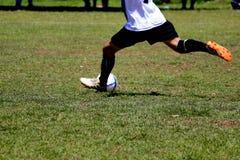 De mensen spelen voetbal op een openluchtgazon stock afbeeldingen