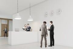 De mensen spreken in een zaal dichtbij ontvangstteller met klokken Royalty-vrije Stock Afbeelding