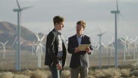 De mensen spreken op het project op het gebied van windmolens stock videobeelden