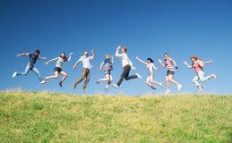 De mensen springen op heuvel over hemel stock afbeelding