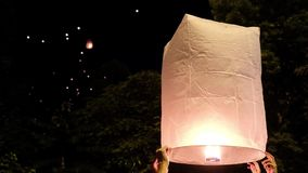De mensen stellen een grote document lantaarn met brand in de nachthemel bij de viering van Loi in werking Krathong tijdens Yee P stock footage