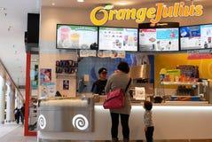 De mensen stellen voor het kopen van drank bij Oranje Julius-opslag op royalty-vrije stock afbeeldingen