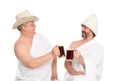 De mensen in traditionele het baden kledij drinken kvas stock foto's