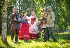 De mensen in traditionele Russische kleren bevinden zich in het hout en het spreken - ??n van hen spelen de harmonika en royalty-vrije stock foto