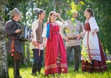 De mensen in traditionele Russische kleren communiceren in het bos op de weide - ??n van hen spelenmuziek op harmonika royalty-vrije stock fotografie