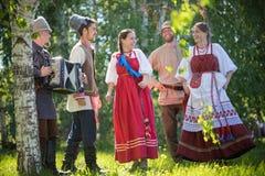 De mensen in traditionele Russische kleren dansen in het gebied en het spreken - ??n van hen spelen de harmonikamuziek stock afbeelding