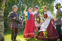 De mensen in traditionele Russische kleren dansen in het hout - ??n van hen spelen de harmonika en het zingen stock foto
