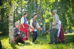 De mensen in traditionele Russische kleren spreken op het gebied en hebben pret - ??n van hen spelen de harmonika en stock foto