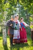 De mensen in traditionele Russische kleren zijn tribune onder een berkboom en het glimlachen - ??n van hen spelen de harmonika royalty-vrije stock foto