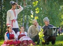 De mensen in traditionele Russische kleren zitten op het gazon - ??n van hen spelen de harmonika royalty-vrije stock foto