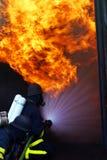 De mensen van de brand in actie het branden de bouw Stock Afbeeldingen