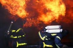 De mensen van de brand in actie het branden de bouw Stock Afbeelding