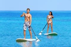 De mensen van het Paddleboardstrand op tribune op peddelraad Royalty-vrije Stock Foto's
