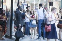 De mensen van verschillende nationaliteiten bevinden zich bij de bushalte die op de bus wachten Stock Afbeelding