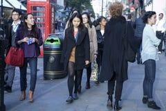 De mensen van verschillende nationaliteiten lopen langs de Straat van Oxford in Londen Stock Foto's