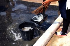 De mensen vegen vuil water bij grondstraten, schonere vloer, dienstmeisje, huishoudster, gezinshulp, hulpje, meisje royalty-vrije stock foto
