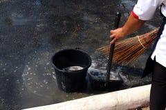 De mensen vegen vuil water bij grondstraten, schonere vloer, dienstmeisje, huishoudster, gezinshulp, hulpje, meisje royalty-vrije stock fotografie
