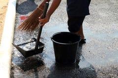 De mensen vegen vuil water bij grondstraten, schonere vloer, dienstmeisje, huishoudster, gezinshulp, hulpje, meisje stock fotografie