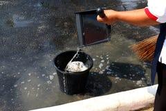 De mensen vegen vuil water bij grondstraten, schonere vloer, dienstmeisje, huishoudster, gezinshulp, hulpje, meisje stock foto
