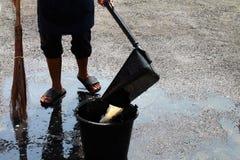 De mensen vegen vuil water bij grondstraten, schonere vloer, dienstmeisje, huishoudster, gezinshulp, hulpje, meisje stock afbeelding