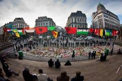 De mensen verzamelden zich voor de Beurs van Brussel om de slachtoffers van de terroristische aanslagen van 22 Maart, 2016 te her Stock Afbeelding