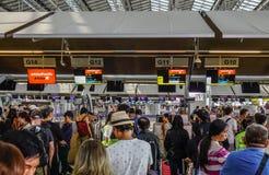 De mensen wachten in lijn om hun luggages te controleren stock afbeeldingen