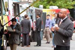 De mensen wachten in Lijn om tot Maaltijd van Voedselvrachtwagens opdracht te geven Royalty-vrije Stock Afbeelding