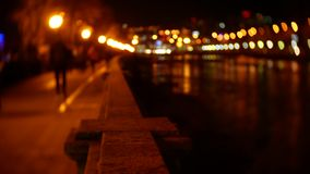 De mensen wandelen langs de dijk die met avondlichten wordt uitgestrooid blur 4K bokeh stock video