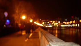 De mensen wandelen langs de dijk die met avondlichten wordt uitgestrooid blur 4K bokeh stock videobeelden