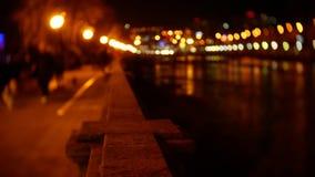 De mensen wandelen langs de dijk die met avondlichten wordt uitgestrooid blur 4K bokeh stock footage