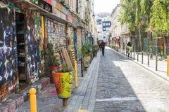 De mensen wandelen onderaan baksteen bedekte die steeg met kleurrijke graffit wordt gevoerd Stock Foto's