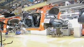 De mensen werken bij assemblage van auto's Lada aan transportband van fabriek AutoVAZ stock video