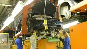 De mensen werken bij assemblage van auto's LADA Granta aan transportband stock videobeelden