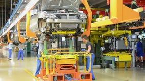 De mensen werken bij assemblage van auto's Lada Kalina aan transportband van fabriek AutoVAZ stock videobeelden